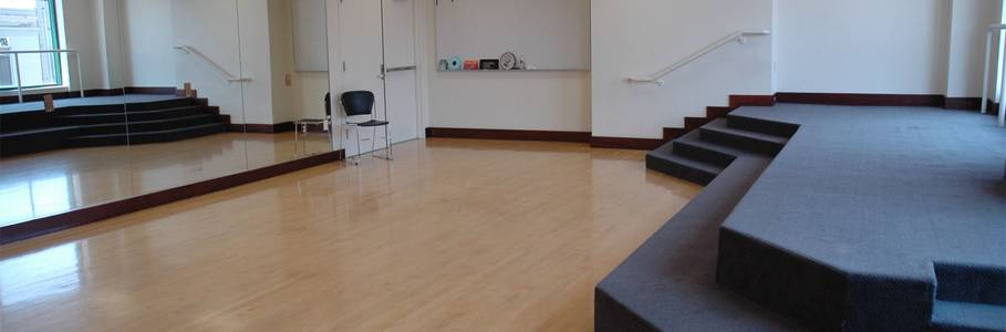 A small stage, full wall mirror, dance barre and writing board make this studio ideal for dance, music and theater classes or rehearsals.
